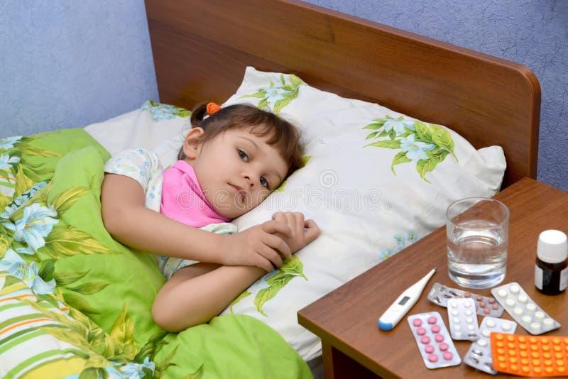 Den lilla ledsna sjuka flickan ligger i en säng arkivfoton
