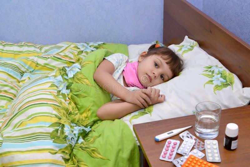 Den lilla ledsna sjuka flickan ligger i en säng arkivbild