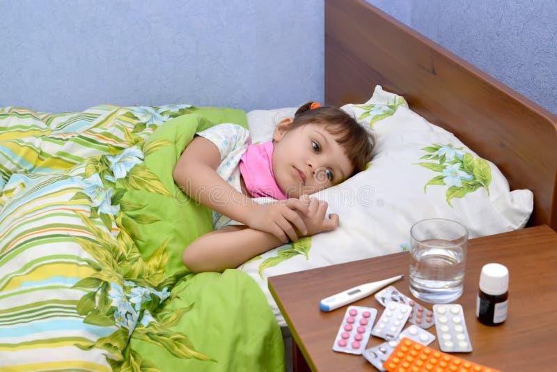 Den lilla ledsna sjuka flickan ligger i en säng royaltyfria bilder
