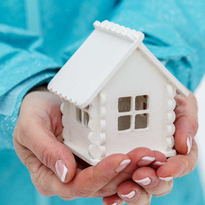 Den lilla leksaken av det vita huset ligger i händerna för kvinna` s arkivfoton