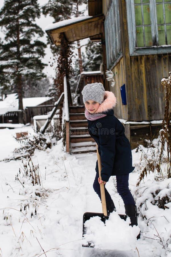 Den lilla lyckliga flickan gör ren snö nära ett hans lantligt hus arkivbild
