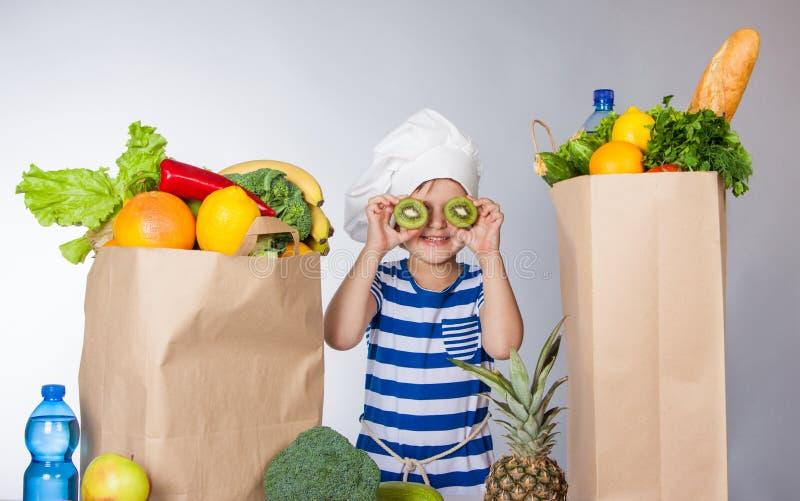 Den lilla lyckliga flickan i kockhatt med stora packar av produkter och den skivade kiwin nära synar arkivfoto