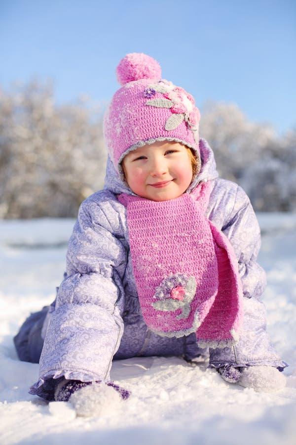 Den lilla lyckliga flickan i rosa halsduk och hatt ligger på snö royaltyfria foton