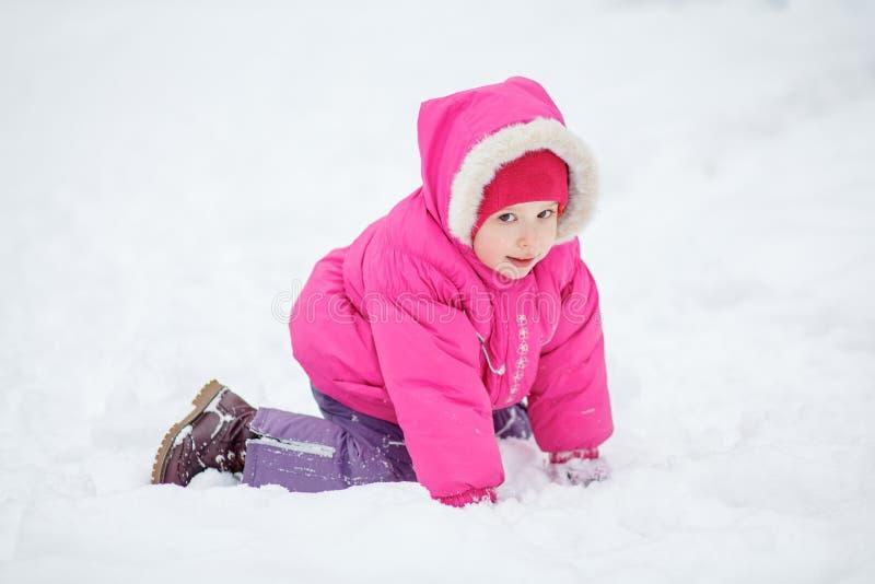 Den lilla lyckliga flickan ligger på snö royaltyfri bild