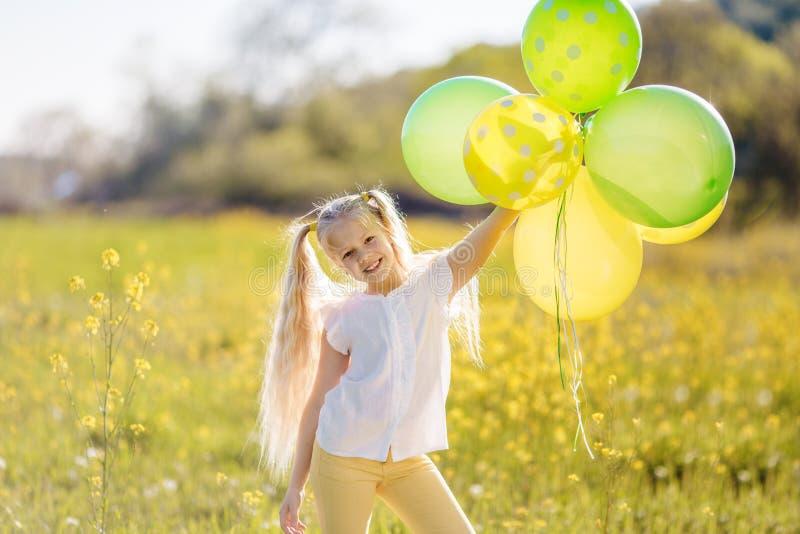 Den lilla lyckliga flickan med gräsplan och guling sväller arkivbilder