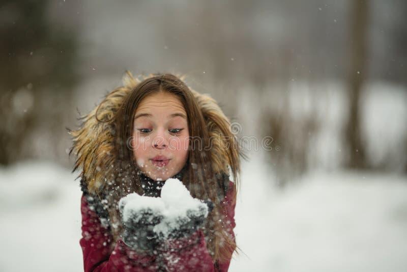 Den lilla lyckliga flickan tycker om insnöad fantastisk vinter arkivbilder