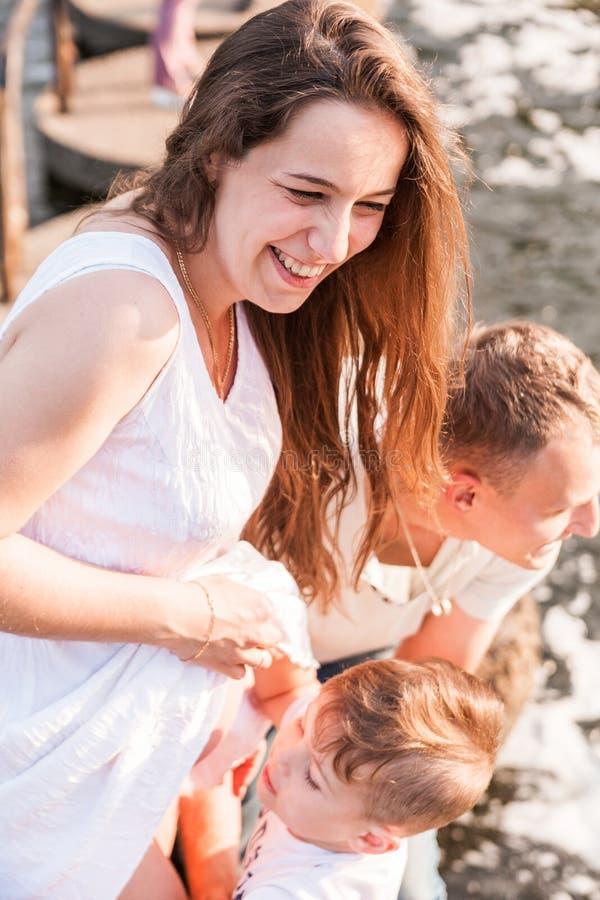 Den lilla lyckliga pojken trycker p? mammans gravida buk royaltyfri fotografi