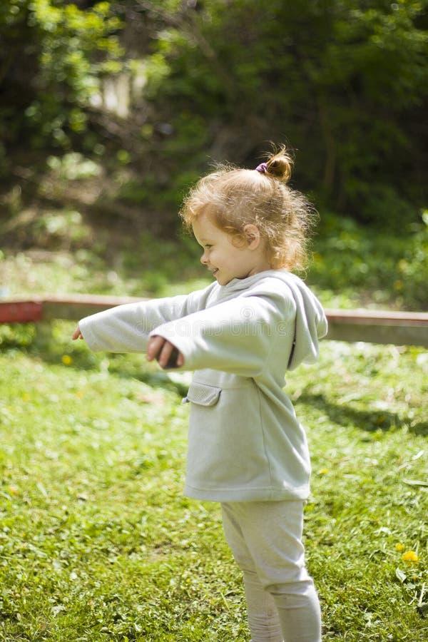 Den lilla lyckliga rödhåriga flickan fördelade hennes armar till den varma vårsolen och värma sig i lekplatsen arkivbilder