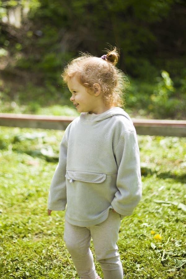 Den lilla lyckliga rödhåriga flickan värma sig i den varma vårsolen på lekplatsen royaltyfria bilder