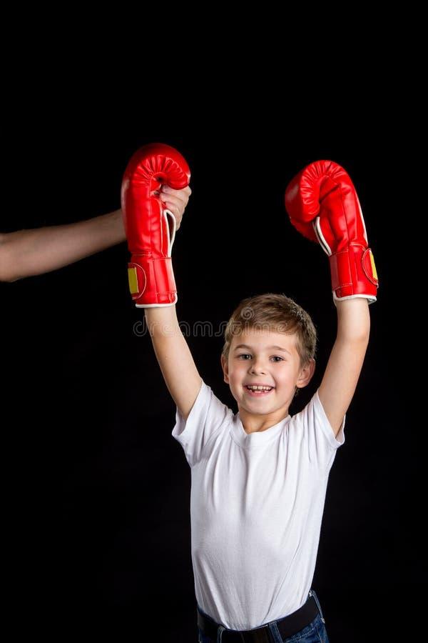 Den lilla mästaren med lagledareservice Extremt lycklig liten boxare med händer upp i röda boxninghandskar fotografering för bildbyråer