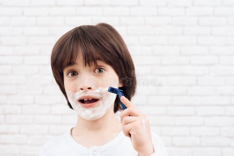 Den lilla mörker-haired pojken lär att raka Han har att raka stelnar på hans framsida och en rakkniv i hans hand royaltyfri fotografi