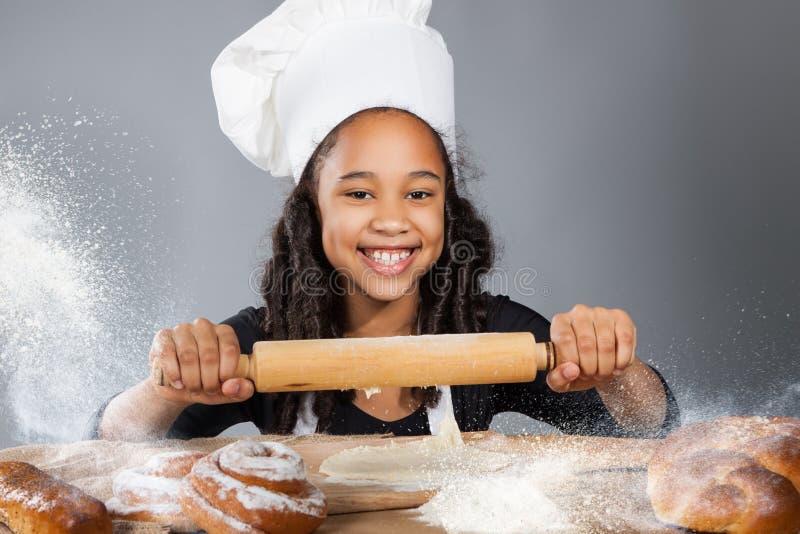 Den lilla mörkhyade flickan rullar degen Barnet lär att laga mat Kläd- och kockhatt arkivbild