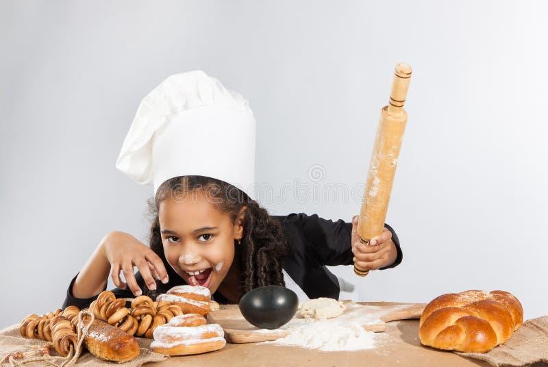Den lilla mörkhyade flickan rullar degen Barnet lär att laga mat Kläd- och kockhatt arkivbilder