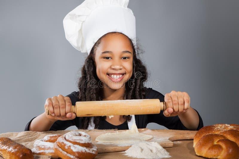 Den lilla mörkhyade flickan rullar degen Barnet lär att laga mat Kläd- och kockhatt royaltyfria foton