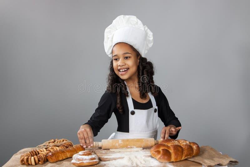 Den lilla mörkhyade flickan rullar degen Barnet lär att laga mat Kläd- och kockhatt arkivfoto