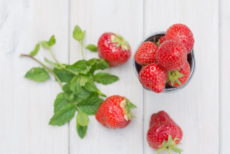 Den lilla metallhinken fyllde med jordgubbar och en kvist av mintkaramellen arkivfoton