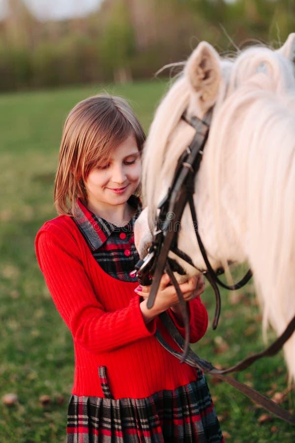 Den lilla modellen av ett ung flickabarn ser en vit häst royaltyfria foton