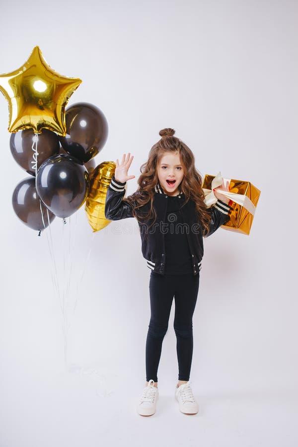 Den lilla moderna hipsterflickan i modekläder står nära ballonger och rymmer guld närvarande Posera framsidan Födelsedag arkivfoton