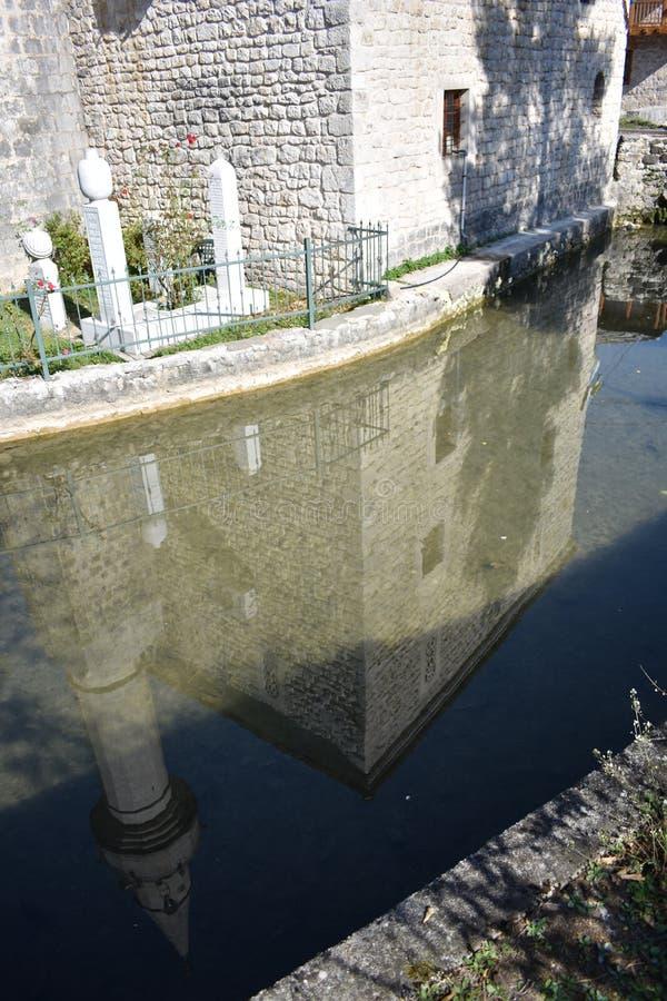 Den lilla moskén i Stolac och reflexionen i den Bregava floden arkivfoton
