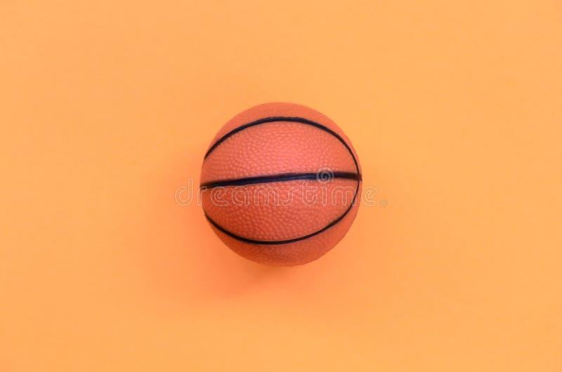 Den lilla orange bollen för basketsportlek ligger på texturbakgrund av pastellfärgat orange färgpapper för mode i minsta begrepp fotografering för bildbyråer