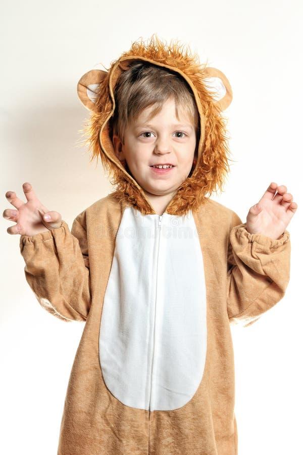 Den lilla pojken i lejonlag med jordluckrare fingrar royaltyfri foto