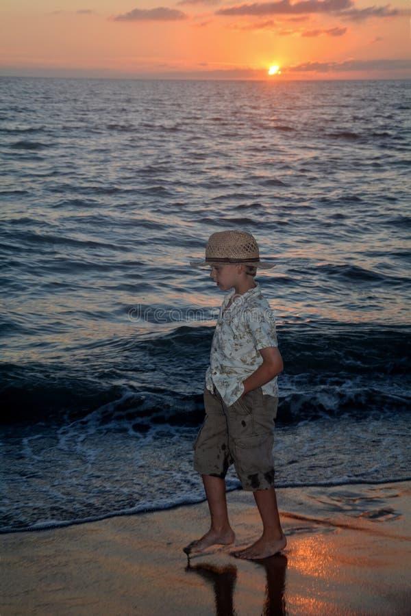 Den lilla pojken kör på solnedgången längs stranden royaltyfri bild