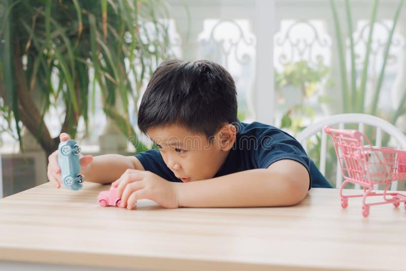 Den lilla pojken leker med billeksaken på bordet arkivfoto