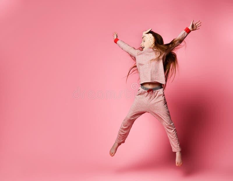 Den lilla rödhåriga flickan i gullig pyjamas och hår förbinder att hoppa arkivbild