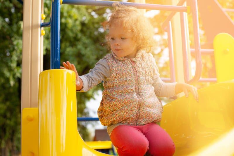 Den lilla rödhåriga flickan sitter på en kulle i barn parkerar och värma sig i det varma solskenet royaltyfri fotografi