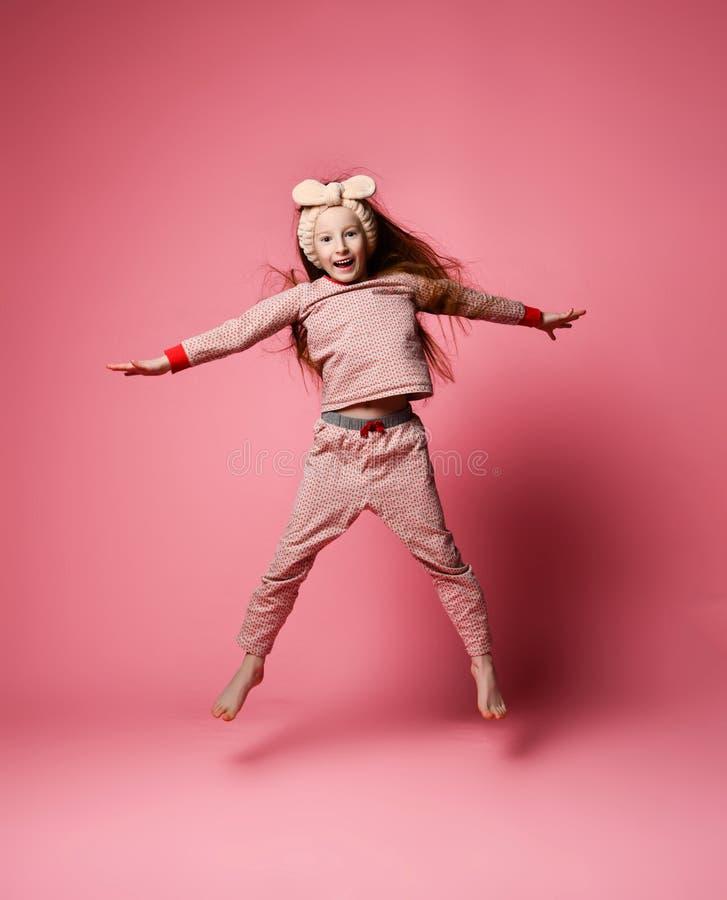 Den lilla r?dh?riga flickan i gullig pyjamas och h?r f?rbinder att hoppa royaltyfri fotografi