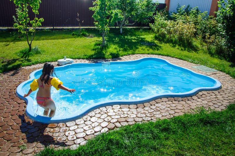 Den lilla roliga flickan är simbassängen royaltyfri bild