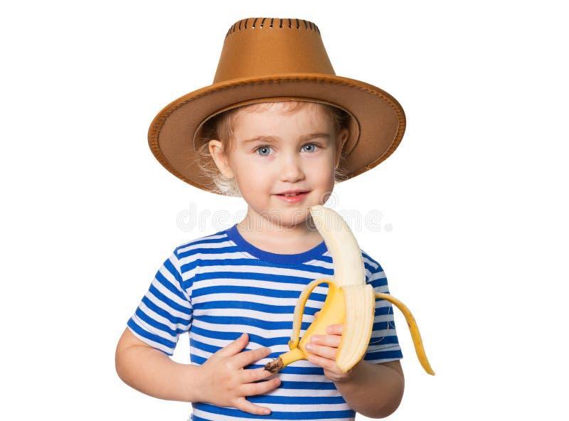 Den lilla roliga flickan äter bananen arkivbild