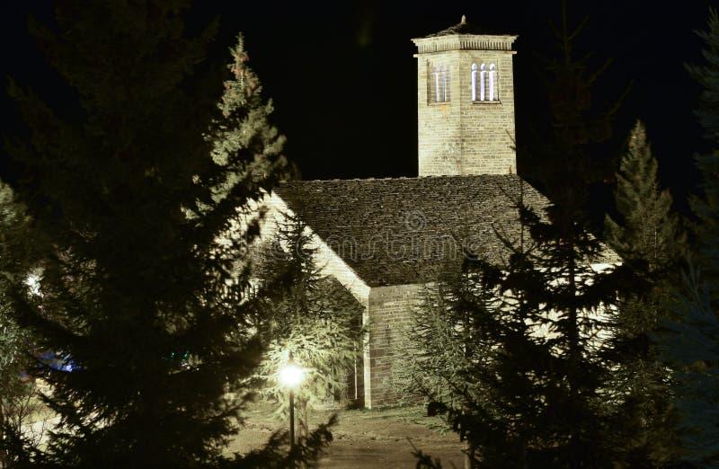 den lilla romanesquekyrkan med dess typiska torn gjorde sammanlagt stenar i mitt av en skog exponerad vid natt arkivfoton