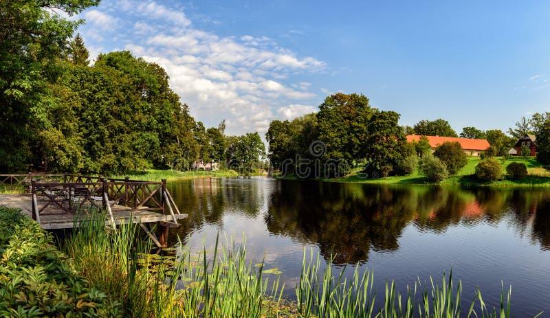 Den lilla sjön med träbron i höst parkerar i Lettland arkivbilder