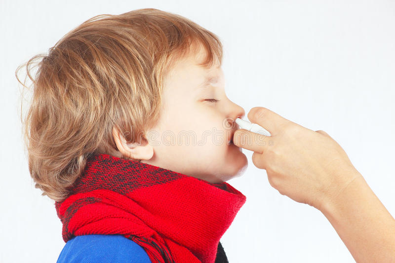 Den lilla sjuka pojken använde nasal sprej i näsan royaltyfria foton