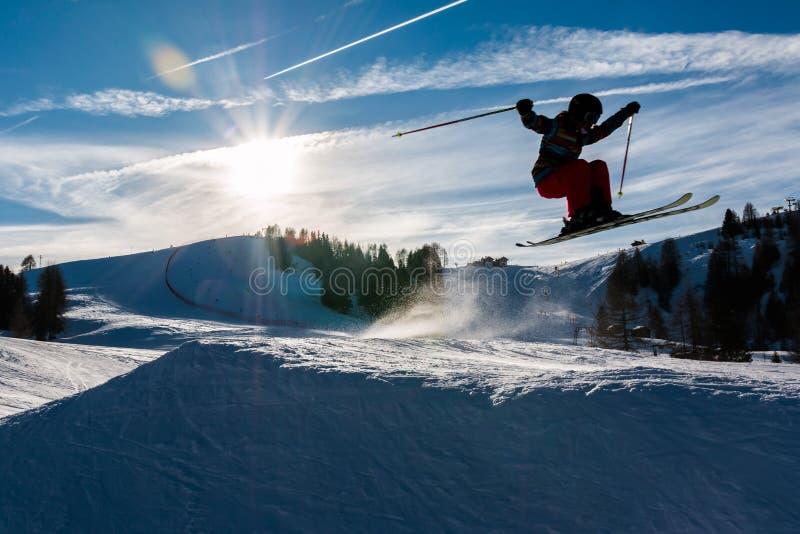 Den lilla skidåkaren utför hopp i snön royaltyfri bild