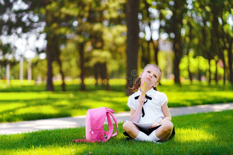 Den lilla skolaflickan med den rosa ryggsäcken som sitter på gräs efter kurser och tänkande idéer, läste bok- och studiekurser fotografering för bildbyråer