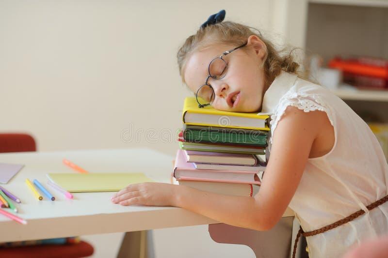 Den lilla skolflickan faller sovande på en hög av böcker arkivfoton