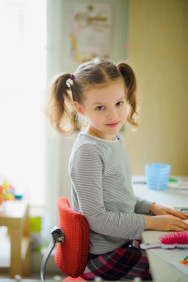 Den lilla skolflickan utför läxa fotografering för bildbyråer