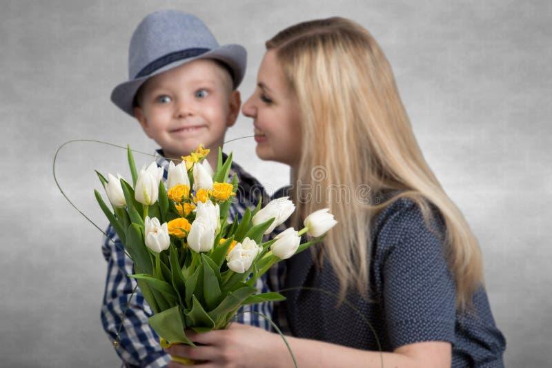 Den lilla sonen ger hans älskade moder en bukett av härliga tulpan Vår begrepp av familjsemestern Bukett av blommacloseupen royaltyfri bild