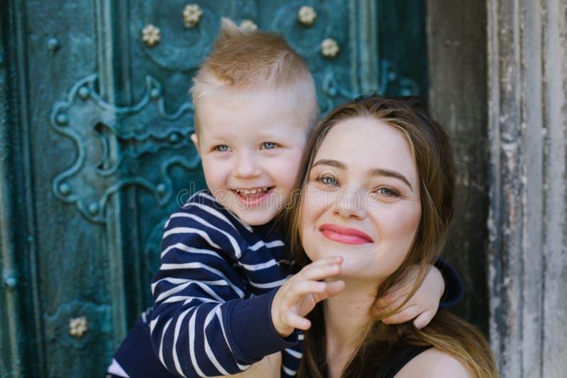 Den lilla sonen kramar mamman Begrepp av förälskelse, familjen, uppfostran och livsstilen royaltyfri bild