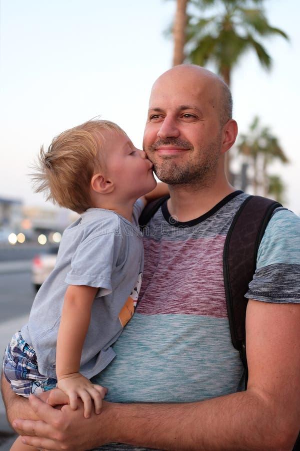Den lilla sonen kysser hans fader på en kind royaltyfri foto