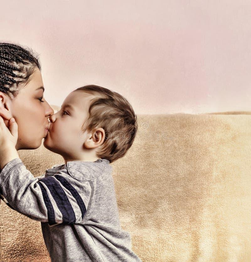 Den lilla sonen kysser hans moder close upp royaltyfria bilder