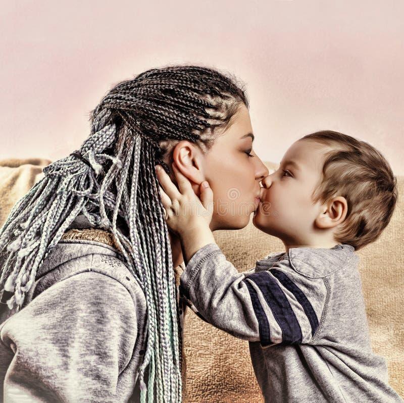 Den lilla sonen kysser hans moder close upp royaltyfri bild