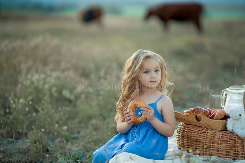 Den lilla stilfulla ungen som bär den moderiktiga kontrollerade skjortan och jeans, har gyckel på picknicken Han dricker yoghurt  royaltyfri fotografi