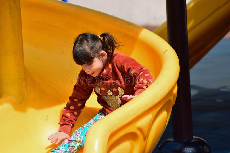 Den lilla stygga flickan som spelar på lekplatsen i staden, parkerar royaltyfria foton