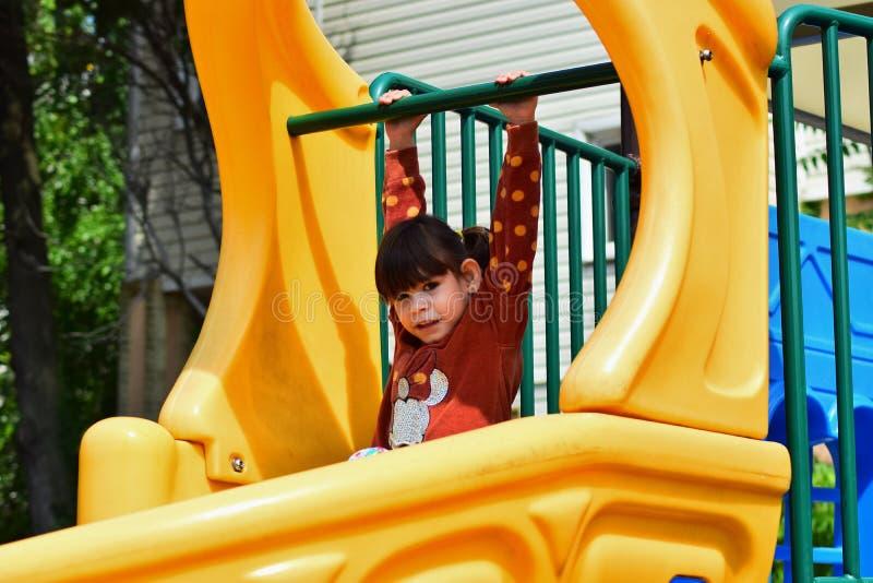 Den lilla stygga flickan som spelar på lekplatsen i staden, parkerar fotografering för bildbyråer