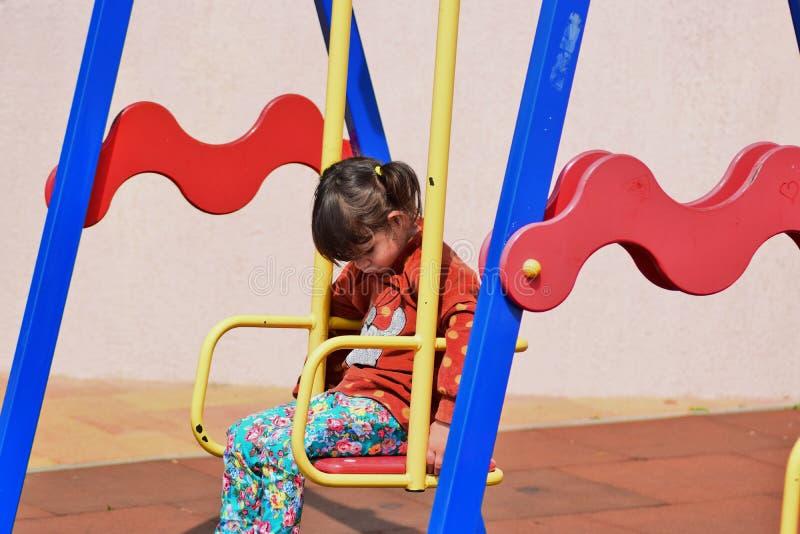 Den lilla stygga flickan som spelar på lekplatsen i staden, parkerar royaltyfri foto