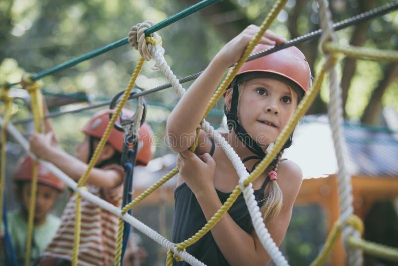 lillebror och syster klättrar i äventyrsparken arkivbild