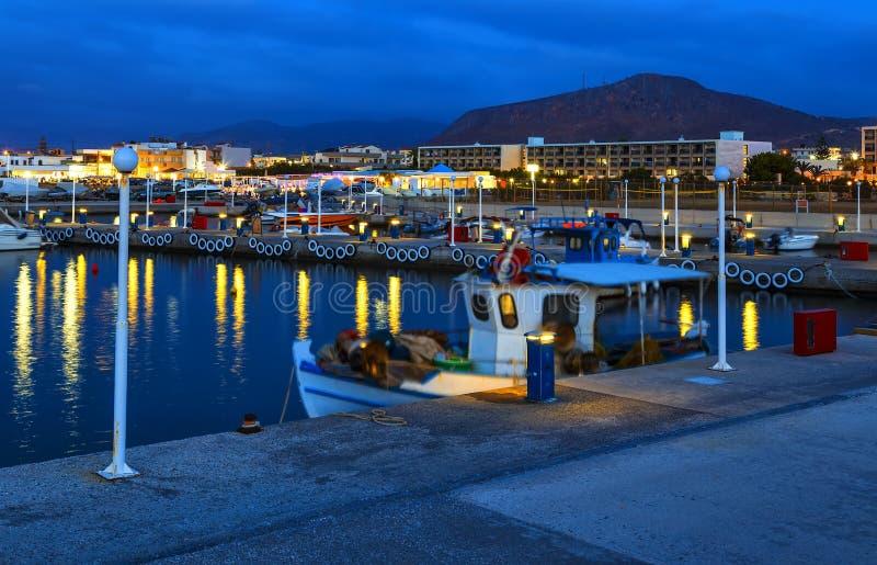 Den lilla traditionella hamnen med skepp och fartyg på pir på solnedgången, Kreta, Grekland arkivbild